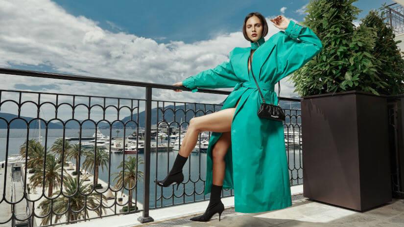 Woman in a green coat posing in Porto Montenegro