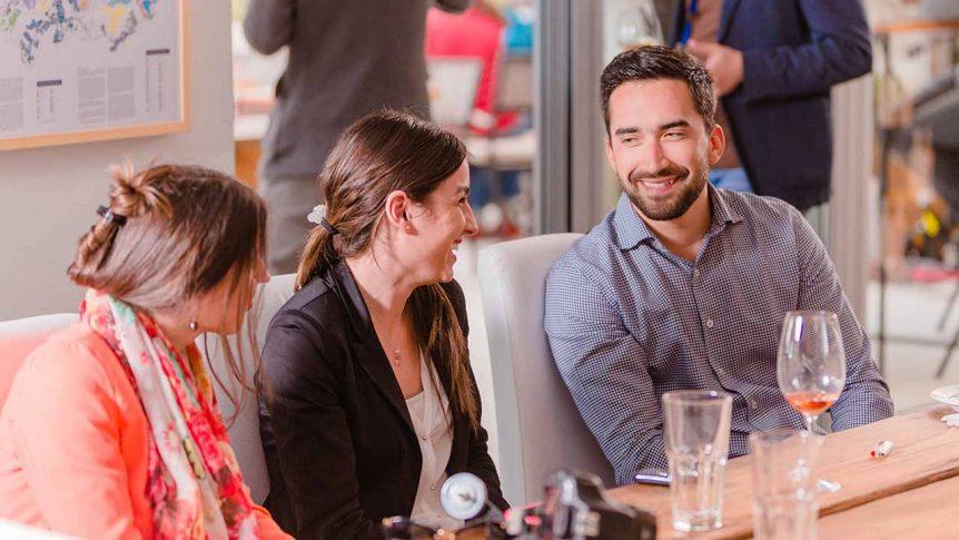 Ljudi sjede za stolom i piju