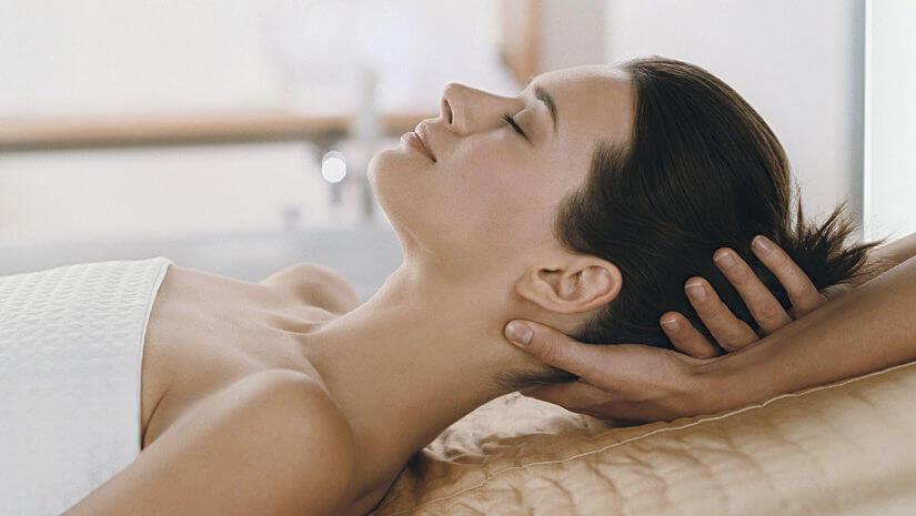 Woman enjoying head massage in spa