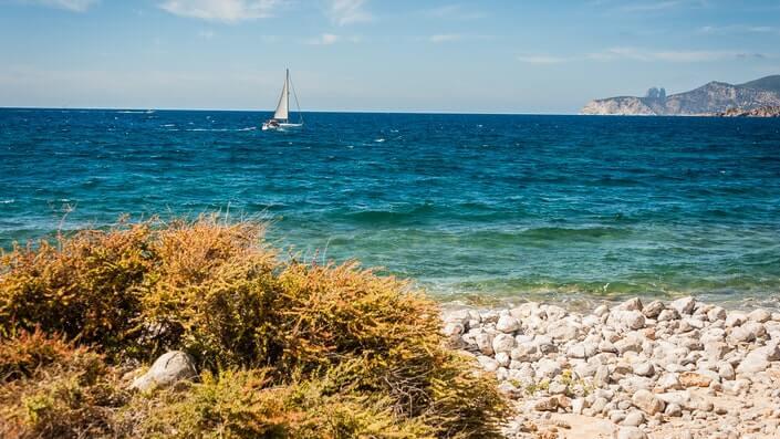 prikaz plaže, mora i brodića u daljini